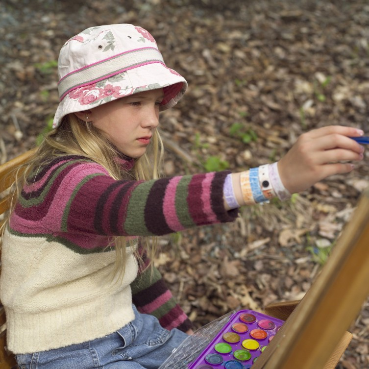 girl painting in the woods