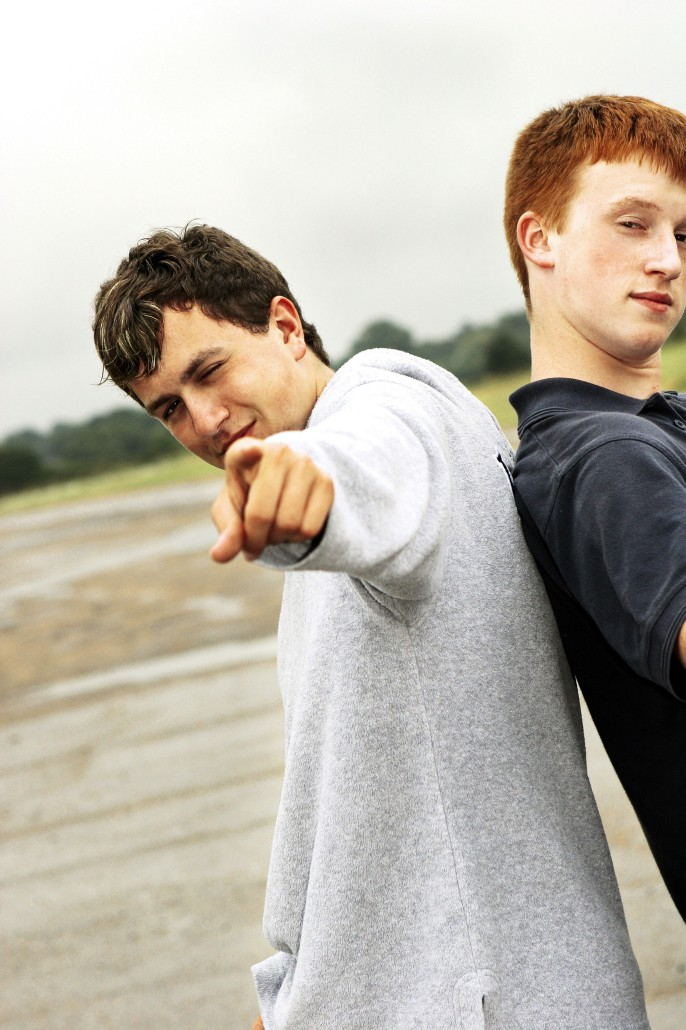 two teens pointing forward