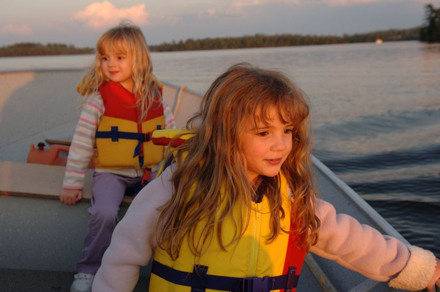 girls with life jackets in boat