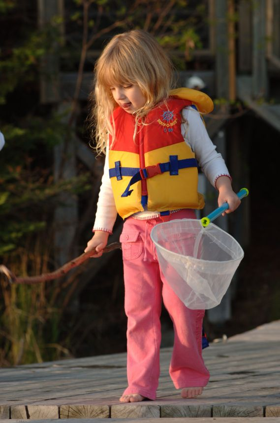girl near water wearing life jacket