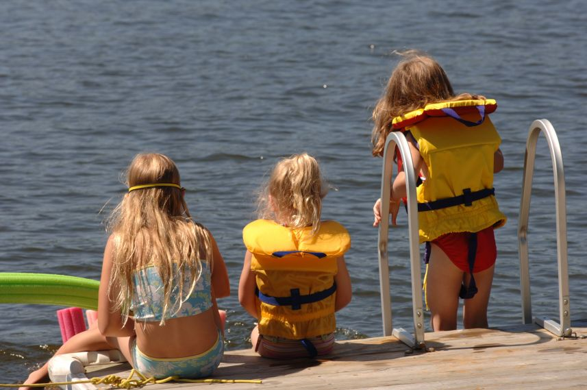 three girls by the water in life jackets