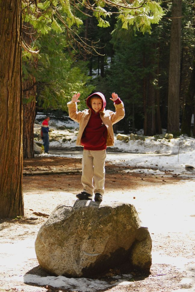 boy standing on a rock triumphant