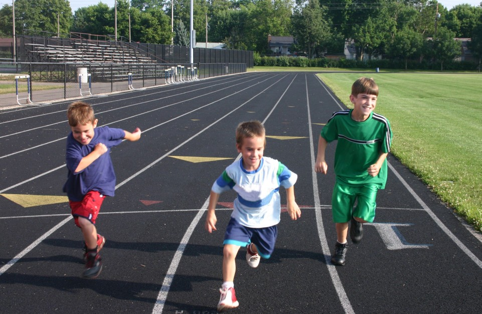 three boys running on a track